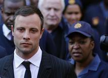 Paralympic track star Oscar Pistorius (L) leaves after the closing arguments in his murder trial at the high court in Pretoria August 8, 2014. REUTERS/Siphiwe Sibeko