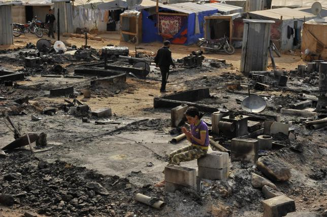 A Syrian refugee girl sits on cement blocks amid damage and burnt tents from the fighting between Lebanese army soldiers and Islamist militants in the Sunni Muslim border town of Arsal, in eastern Bekaa Valley, Lebanon August 7, 2014. REUTERS/Hassan Abdallah