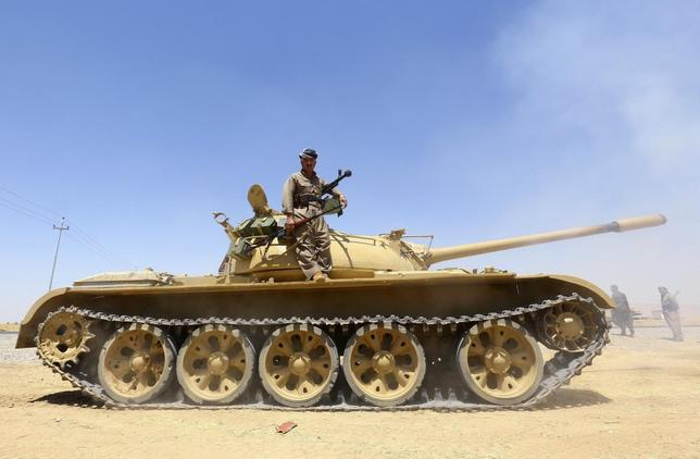 A member of the Kurdish peshmerga troops stands on a tank during an operation against Islamic State militants in Makhmur, on the outskirts of the province of Nineveh August 7, 2014. REUTERS/Stringer