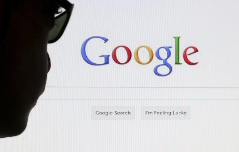 A computer user poses in front of a Google search page in this photo illustration taken in Brussels May 30, 2014.  REUTERS/Francois Lenoir/Files