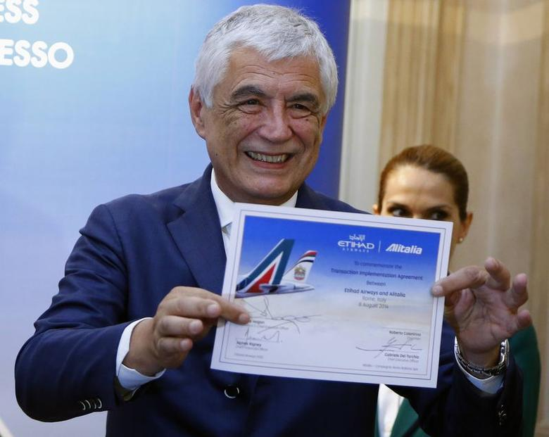 Alitalia Chief Executive Officer Gabriele Del Torchio (R) shows the newly signed contract during a media conference in Rome, August 8, 2014. REUTERS/Stefano Rellandini