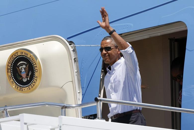 U.S. President Barack Obama waves as he steps from Air Force One upon his arrival at Cape Cod Coast Guard Air Station in Massachusetts August 9, 2014. REUTERS/Kevin Lamarque