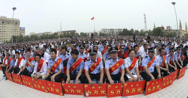Police wearing sashes hold placards during a ceremony to award those who the authorities say participated in ''the crackdown of violence and terrorists activities'' in Hotan, Xinjiang Uighur Autonomous Region August 3, 2014. REUTERS/Stringer
