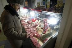 Мужчина смотрит на мясо на рынке в Москве 8 февраля 2013 года. Один из крупнейших производителей мяса в РФ группа Черкизово ожидает позитивного влияния на свой бизнес запрета импорта продовольствия в Россию на фоне обострения отношений с США и ЕС из-за конфликта на Украине, сообщила компания в понедельник. REUTERS/Mikhail Voskresensky