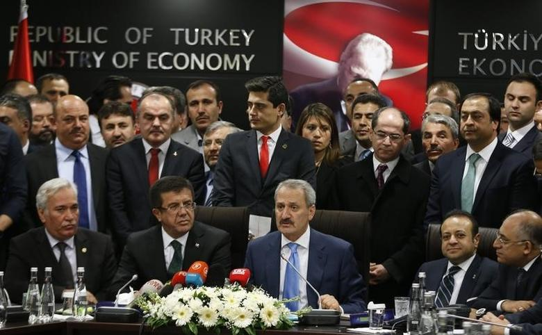 Turkey's outgoing Economy Minister Zafer Caglayan (C) talks during a handover ceremony as he is flanked by newly named minister Nihat Zeybekci (2nd L) and former European Affairs Minister Egemen Bagis (2nd R) in Ankara December 26, 2013.   REUTERS/Umit Bektas