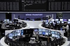 Traders are pictured at their desks in front of the DAX board at the Frankfurt stock exchange August 11, 2014.      REUTERS/Joachim Herrmann/Remote