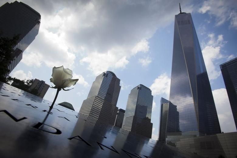 A flower is pictured at the 9/11 Memorial with the One World Trade Center in the background, in New York July 31, 2014. REUTERS/Carlo Allegri/Files