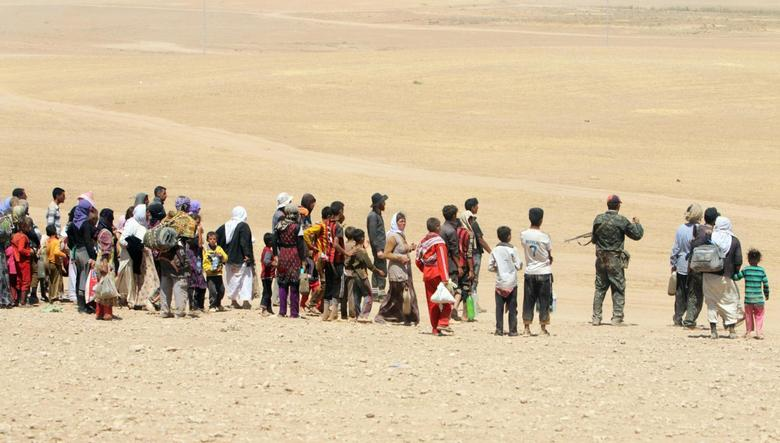 Displaced people from the minority Yazidi sect, fleeing violence from forces loyal to the Islamic State in Sinjar town, make their way towards the Syrian border, on the outskirts of Sinjar mountain, near the Syrian border town of Elierbeh of Al-Hasakah Governorate August 10, 2014.  REUTERS/Rodi Said