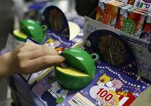 An office worker puts a 100 yen coin into a frog-shaped piggy bank filled with snacks for office workers, Ezaki Glico's kiosks-in-a-box Office Glico, at an office in Tokyo August 8, 2014.   REUTERS/Yuya Shino