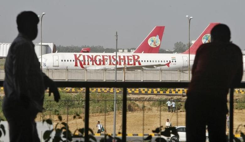 People are silhouetted as Kingfisher Airlines' aircrafts are seen parked at an airport in New Delhi October 1, 2012. REUTERS/Mansi Thapliyal/Files