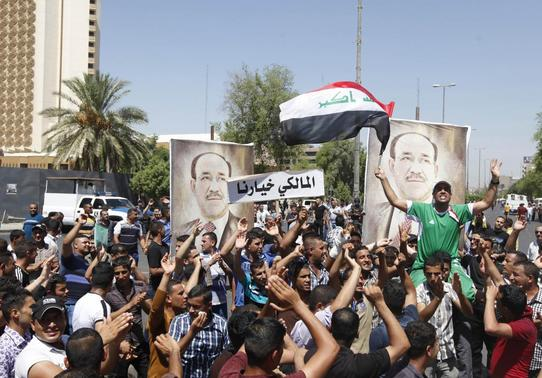 People with portraits of Iraqi Prime Minister Nuri al-Maliki gather at a rally in support of him in Baghdad August 11, 2014. The white banner reads, 'Al-Maliki, our choice'. REUTERS/Ahmed Saad