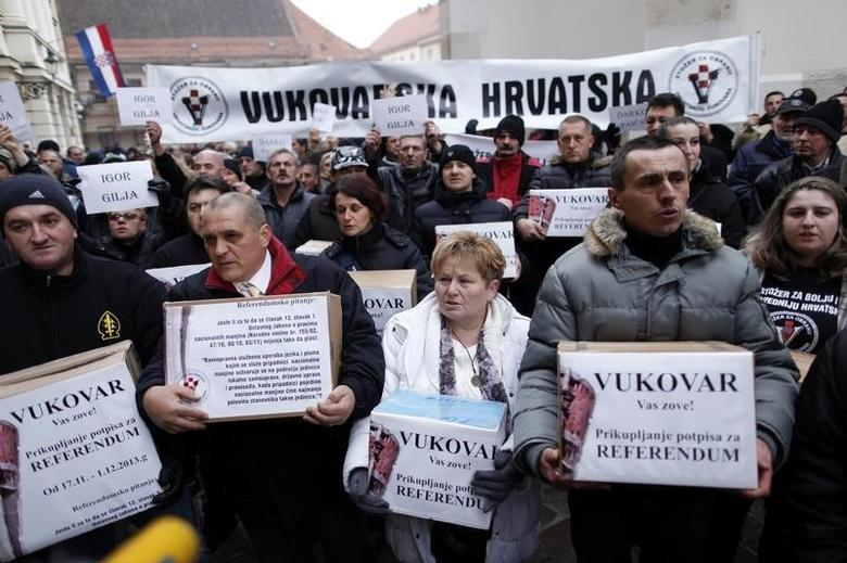 Demonstrators against the use of Serbian Cyrilic script in street signs in the city of Vukovar, carry boxes as they collect signatures to call for a referendum on the issue during a demonstration in downtown Zagreb December 16, 2013.  REUTERS/Antonio Bronic