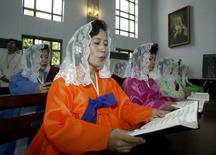 North Koreans read mass at a Catholic church in Pyongyang in this August 17, 2003 file photo.    REUTERS/Lee Jae-won/Files