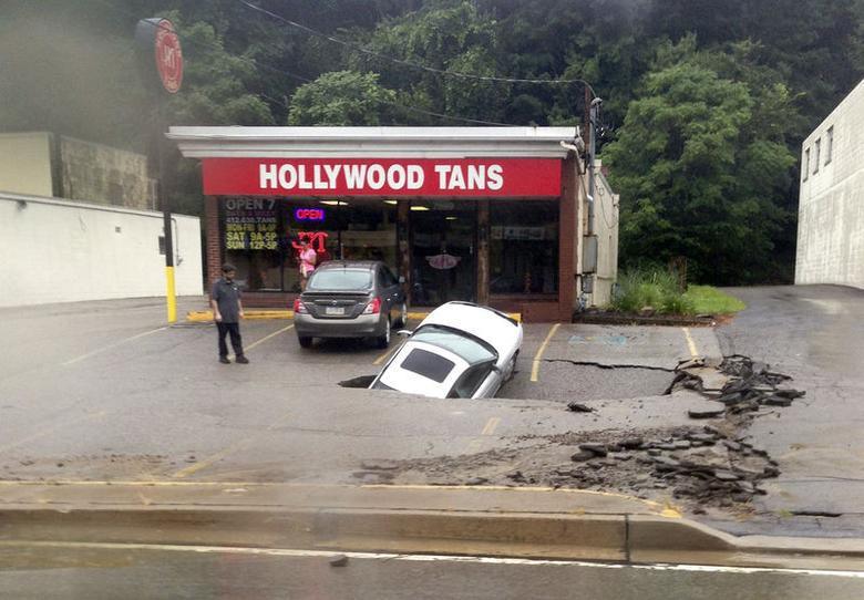 A man looks at a car as it falls into a sinkhole on McKnight Road in Ross Township of Pittsburgh, Pennsylvania, in this handout photo taken August 12, 2014, courtesy of Roxanne Oglesby. REUTERS/Roxanne Oglesby/Handout via Reuters