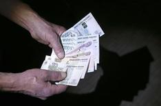 Продавец пересчитывает рублевые купюры в Москве  7 марта 2014 года. Чистая прибыль второго по выручке российского продуктового ритейлера X5 Retail Group во втором квартале 2014 года выросла на 71,2 процента к аналогичному периоду 2013 года до 3,98 миллиарда рублей, сообщила компания в четверг. REUTERS/Sergei Karpukhin