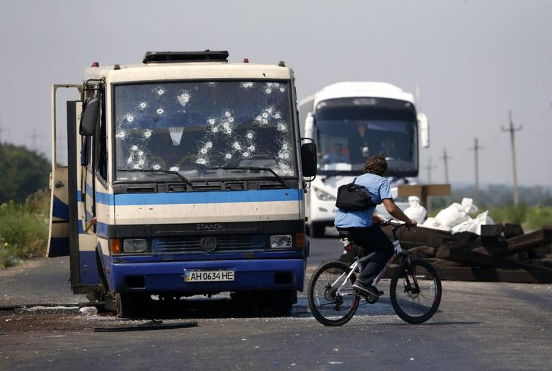 A man rides a bicycle near a bus riddled with bullet holes at a checkpoint on the outskirts of Donetsk, August 13, 2014. REUTERS/Sergei Karpukhin