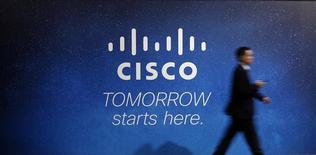 Человек проходит мимо рекламы Cisco на Mobile World Congress в Барселоне 27 февраля 2014 года. Cisco Systems Inc опубликовала умеренный прогноз результатов текущего квартала, сообщив о планах сократить еще 6.000 сотрудников на фоне попыток компании перейти на производство нового поколения сетевых коммутаторов и маршрутизаторов.  REUTERS/Albert Gea