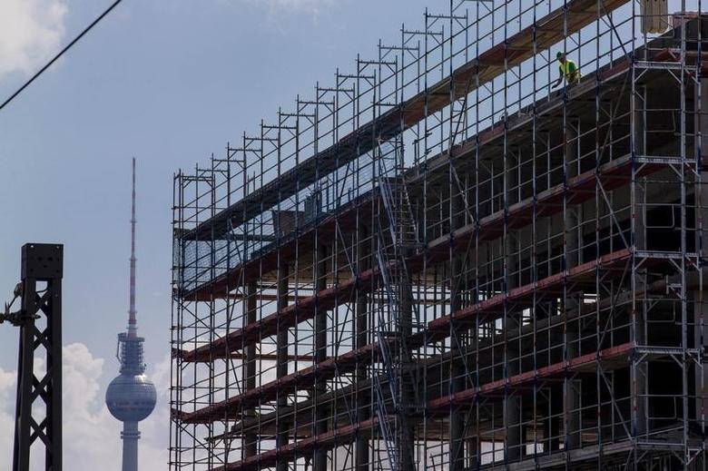 A worker is seen behind scaffoldings at a construction site near the Fernsehturm television tower in Berlin July 7, 2014.REUTERS/Thomas Peter