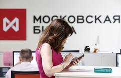 Женщина пользуется телефоном в помещении Московской биржи 3 июня 2014 года. Российские фондовые индикаторы повышаются пятую сессию подряд, и в четверг индекс ММВБ закрепился выше психологически важной отметки в 1.400 пунктов перед выступлением президента РФ Владимира Путина в Крыму. REUTERS/Sergei Karpukhin