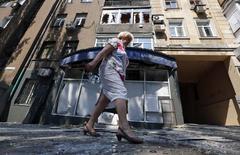 Mulher passa por prédio danificado por disparos de artilharia em Donetsk. 14/08/2014 REUTERS/Sergei Karpukhin