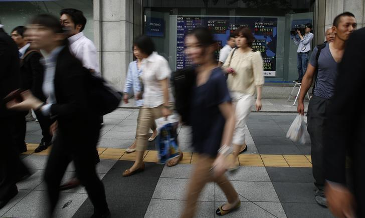 Pedestrians walk past at an electronic board showing the stock market indices of various countries outside a brokerage in Tokyo June 2, 2014. REUTERS/Yuya Shino/Files