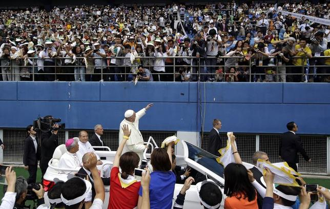 Pope Francis (C) greets faithful as he arrives for the Holy Mass at Daejeon World Cup stadium August 15, 2014. REUTERS/Lee Jin-man/Pool