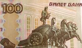 Сторублевая купюра в Москве 8 июля 2014 года. Рубль торгуется с минимальными изменениями к доллару и бивалютной корзине утром пятницы - неопределенность с гуманитарным конвоем и перемещением российской бронетехники на границе с Украиной пока гасит позитивный эффект от налогового периода и глобального спроса на риск, реакции на вчерашние миролюбивые заявления президента РФ. REUTERS/Sergei Karpukhin