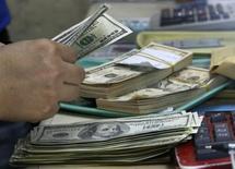 Imagen de archivo de una persona contando dólares en una casa de cambios en Manila, sep 19 2013. Los extranjeros vendieron activos estadounidenses de largo plazo en junio, incluyendo bonos del Tesoro y de empresas de Estados Unidos, lo que revirtió los ingresos de capitales registrados el mes anterior en esa categoría, según datos divulgados el viernes por el Departamento del Tesoro.  REUTERS/Romeo Ranoco