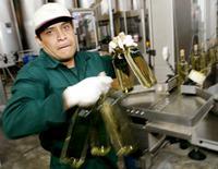 Imagen de archivo de un trabajador en una planta manufacturera de envases de vidrio en Lima, ago 21 2004. La economía de Perú creció un 0,3 por ciento interanual en junio, su menor tasa en casi cinco años, en medio de una caída de sectores primarios clave como el minero y la actividad fabril, lo que abriría la posibilidad de un mayor relajamiento de la política monetaria. REUTERS/Pilar Olivares