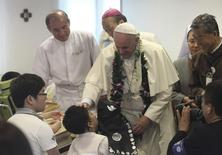 Pope Francis blesses a disabled child during his visit to the rehabilitation center for disabled people at Kkottongnae in Eumseong,  August 16, 2014. REUTERS/Ahn Young-joon/Pool