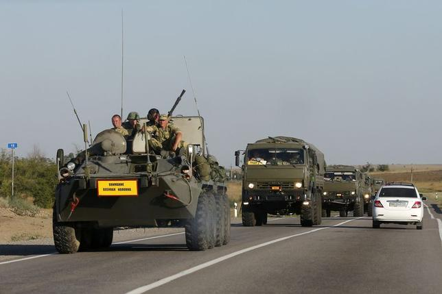Russian servicemen ride atop an armoured personnel carrier (APC) as they escort a column of military vehicles outside Kamensk-Shakhtinsky, Rostov Region, August 15, 2014.  REUTERS/Maxim Shemetov