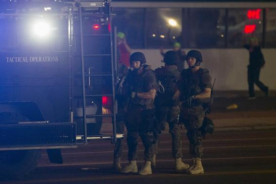 Police officers seek cover behind emergency vehicles after protests turned violent in reaction to the shooting of Michael Brown, in Ferguson, Missouri August 17, 2014.  REUTERS-Lucas Jackson