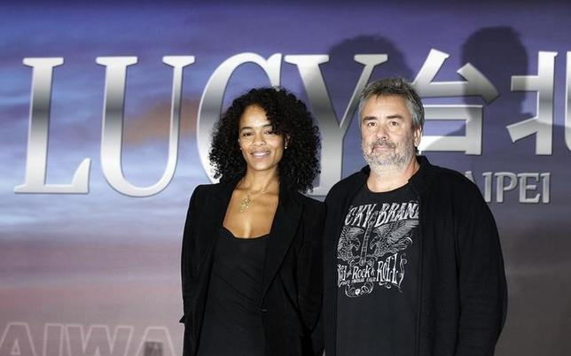 French film director Luc Besson (R) and his wife and producer Virginie Silla pose for photographs during a news conference for his movie ''Lucy'' in Taipei November 1, 2013.  REUTERS/Pichi Chuang