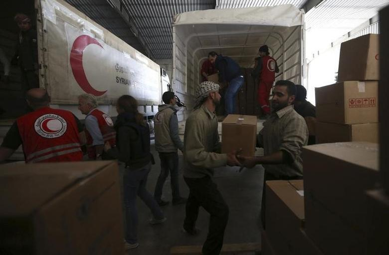 Workers unload bags of humanitarian aid inside a warehouse in the Duma neighbourhood of Damascus March 20, 2014.  REUTERS/Bassam Khabieh