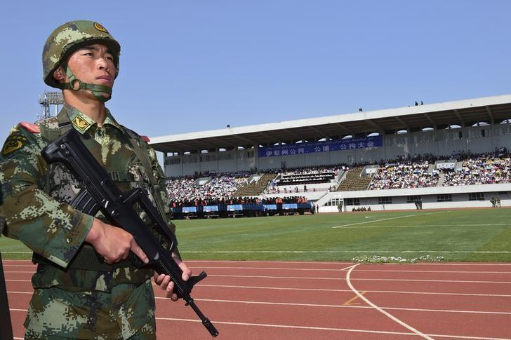 A paramilitary policeman stands guard near trucks carrying criminals and suspects during a mass sentencing rally at a stadium in Yili, Xinjiang Uighur Autonomous Region May 27, 2014.  REUTERS/Stringer
