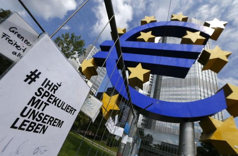 A placard reading ''You speculate with our lives'' stands next to huge euro logo in front of the headquarters of the European Central Bank (ECB) before the bank's monthly news conference in Frankfurt August 7, 2014.      REUTERS/Ralph Orlowski