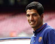 FC Barcelona's Luis Suarez smiles during his presentation at the Nou Camp stadium in Barcelona August 19, 2014. Suarez was officially presented as a Barcelona player on Tuesday while he is still banned for biting Giorgio Chiellini in Uruguay's World Cup game with Italy on June 24. REUTERS/Gustau Nacarino (SPAIN - Tags: SPORT SOCCER)