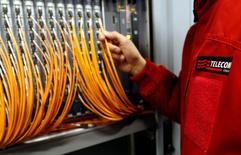 Un técnico de Telecom Italia trabaja con cables de fibra óptica en un terminal telefónico en Roma, dic 20 2013. El directorio de Telecom Italia celebrará una reunión  la próxima semana para discutir una oferta de adquisición del operador de banda ancha brasileño GVT, perteneciente a Vivendi SA, dijo una fuente cercana al asunto el martes.  REUTERS/Alessandro  Bianchi