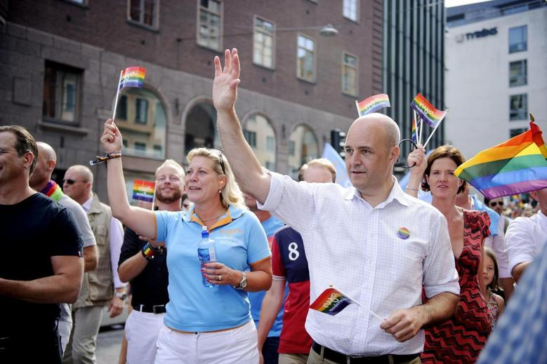 Swedish Prime Minister Fredrik Reinfeldt (R) and Energy Minister Catharina Elmsater-Svard (L) head the government section of the annual gay pride parade in Stockholm August 2, 2014. REUTERS/Annika Af Klercker/TT News Agency