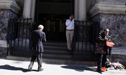 A blind man (R) begs for money at the front entrance of Argentina's Central Bank in Buenos Aires' financial district, August 20, 2014. REUTERS/Marcos Brindicci