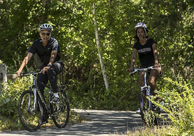 U.S. President Barack Obama cycles with his daughter Malia during their family vacation at Martha's Vineyard in Massachusetts August 15, 2014. REUTERS/Kevin Lamarque