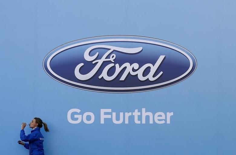 A woman has a drink as she walks past a logo of carmaker Ford at the entrance to a media event in Sydney August 13, 2013.  REUTERS/Daniel Munoz