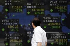 Мужчина у брокерской конторы в Токио 8 августа 2014 года. Азиатские фондовые рынки, кроме Японии, снизились в четверг из-за замедления роста производственной активности Китая. REUTERS/Yuya Shino