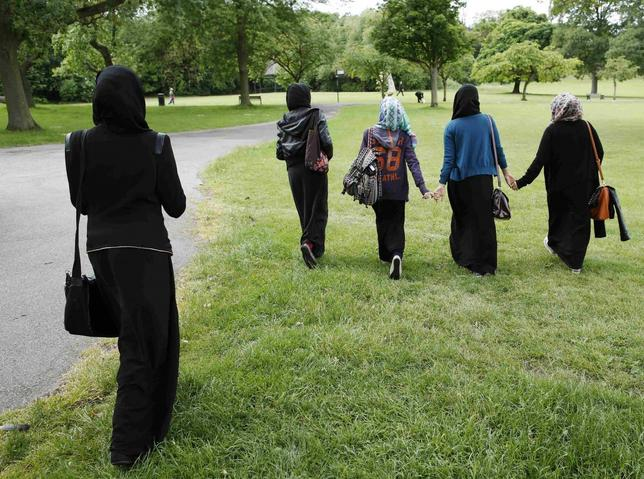 Yasmin (2nd L), 16, Hana (C), 16, and their friends walk in the park after finishing a GCSE exam near their school in Hackney, east London June 6, 2013. REUTERS/Olivia Harris/Files