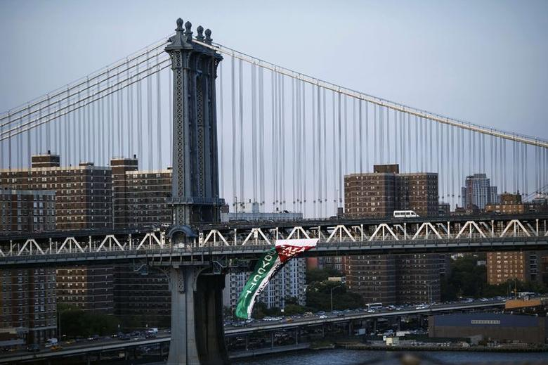 A pro-Palestinian flag is seen hanging from the Manhattan Bridge while pro-Palestinian demonstrators march across the Brooklyn Bridge in Manhattan, New York August 20, 2014. REUTERS/Eduardo Munoz