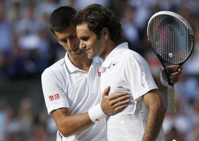 Novak Djokovic of Serbia speaks with Roger Federer of Switzerland after defeating him in their men's singles finals tennis match on Centre Court at the Wimbledon Tennis Championships in London July 6, 2014.         REUTERS/Pool