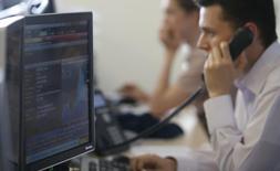 Трейдеры на Московской бирже 3 июня 2014 года. Российские фондовые индексы начали торги пятницы недалеко от сложившихся уровней после роста во все предыдущие дни этой недели. REUTERS/Sergei Karpukhin