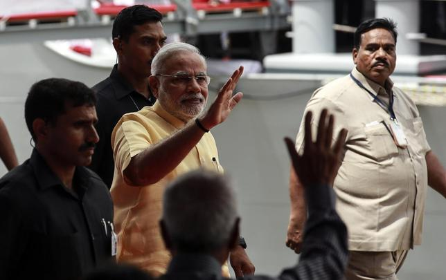 Indian Prime Minister Narendra Modi waves as he leaves after the commissioning ceremony of warship, INS Kolkata at a naval base in Mumbai August 16, 2014. REUTERS/Danish Siddiqui