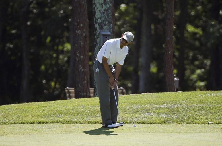 U.S. President Barack Obama lines up his putt while playing a round of golf at Farm Neck Golf Club in Oak Bluffs on Martha's Vineyard, Massachusetts August 9, 2014.  REUTERS/Kevin Lamarque
