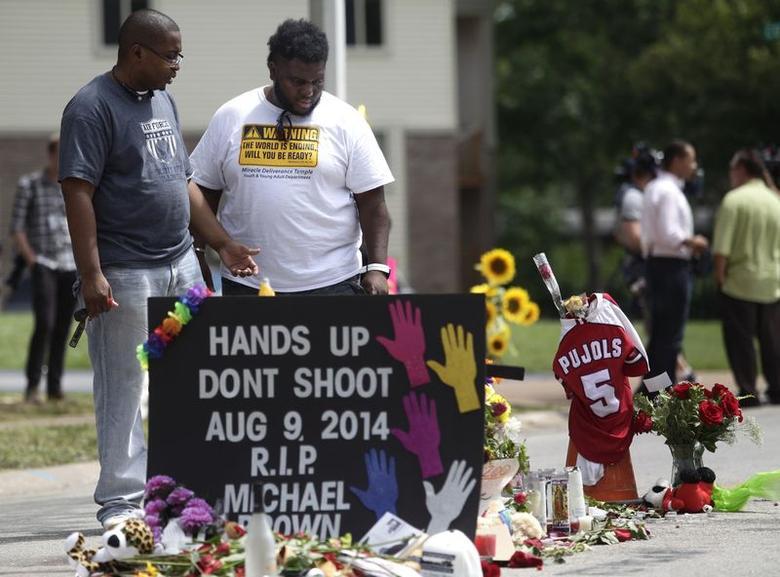 Two men stand over the makeshift memorial for Michael Brown in Ferguson, Missouri August 19, 2014. REUTERS/Joshua Lott